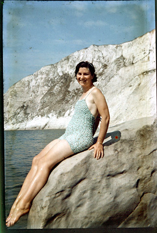 Dufaycolor transparency of woman in swimming costume on rock with sea. Circa 1936.